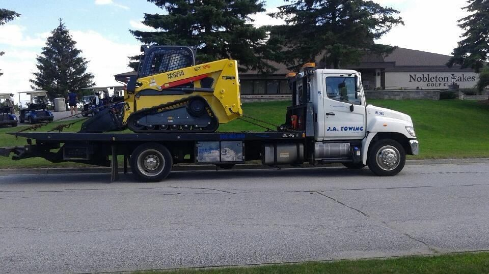 truck towing a mini excavator
