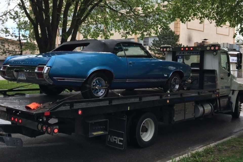 truck towing a blue car